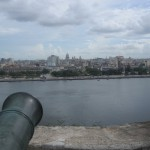 A cannon looks over the city across the river